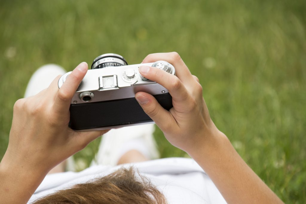 girl holding vintage camera against green meadow